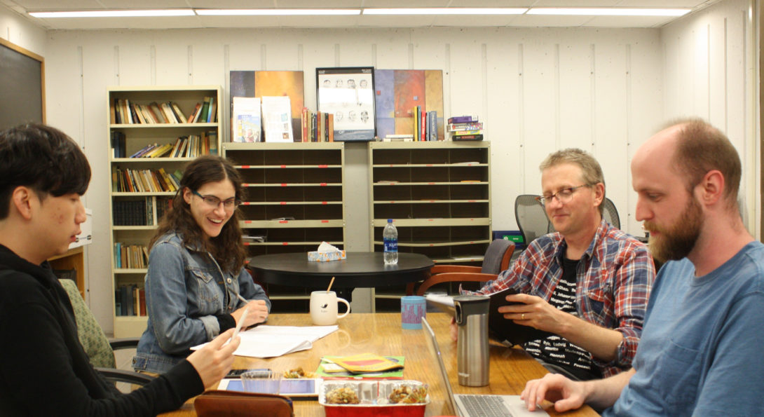 Four people gather around a table and read together.
